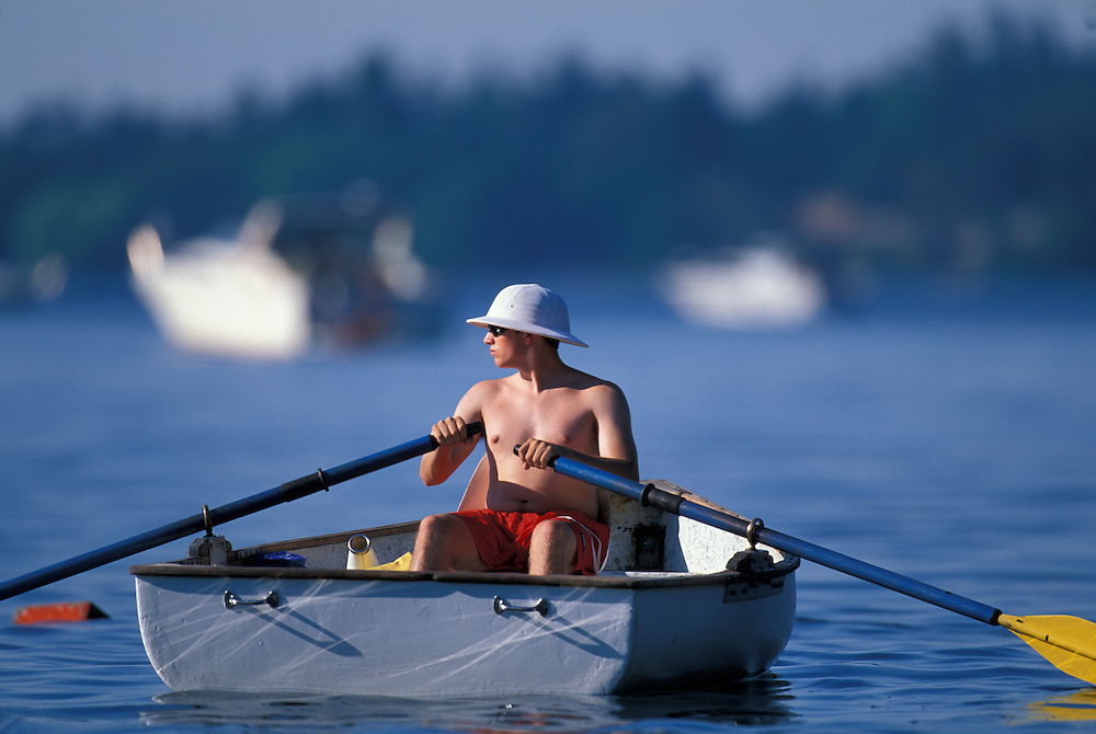 USA, Washington, Seattle, Lifeguard rows boat on lake at Seward Park on summer afternoon