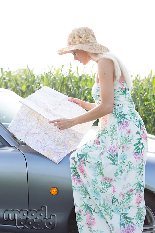 Side view of woman reading map while sitting on convertible