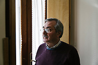 "SUTERA, ITALY - 8 JANUARY 2018: Mayor of Sutera Giuseppe Grizzanti (63) poses for a portrait on the balcony of the town hall of Sutera, Italy, on January 8th 2018.<br /> <br /> Sutera is an ancient town plastered onto the side of an enormous monolithic rock, topped with a convent, in the middle of the western half of Sicily, about 90 minutes by car south of the Sicilian capital Palermo<br /> Its population fell from 5,000 in 1970 to 1,500 today. In the past 3 years its population has surged  after the local mayor agreed to take in some of the thousands of migrants that have made the dangerous journey from Africa to the Sicily.<br /> <br /> ""Sutera was disappearing,"" says mayor Giuseppe Grizzanti. ""Italians, bound for Germany or England, packed up and left their homes empty. The deaths of inhabitants greatly outnumbered births. Now, thanks to the refugees, we have a chance to revive the city.""<br />  Through an Italian state-funded project called SPRAR (Protection System for Refugees and Asylum Seekers), which in turn is co-funded by the European Union's Fund for the Integration of non-EU Immigrants, Sutera was given financial and resettlement assistance that was co-ordinated by a local non-profit organization called Girasoli (Sunflowers). Girasoli organizes everything from housing and medical care to Italian lessons and psychological counselling for the new settlers.<br /> The school appears to have been the biggest beneficiary of the refugees' arrival, which was kept open thanks to the migrants.<br /> Nunzio Vittarello, the coordinator of the E.U. project working for the NGO ""I Girasoli"" says that there are 50 families in Sutera at the moment."