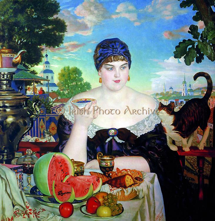 The Merchant's Wife', 1918. Oil on canvas. Boris Kustodiev (1878-1927) Russian painter and stage designer. Woman on balcony sitting at table laden with fruit and cake, holding saucer of food for pet cat. Plenty Excess Voluptuous