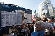 A woman has a puppet rat in a picture of the White House at the Vote Out the Scandal rally at Hachiko Square, Shibuya, Tokyo, Japan. Sunday November 5th 2017. Timed to coincide with President Trumps visit to Japan, About 120 Americans living in Japan and some local Japanese  protested together from 2pm to 4pm to encourage US citizens to register to vote in future elections and call on the US government to honour it responsibilities to the American people,.