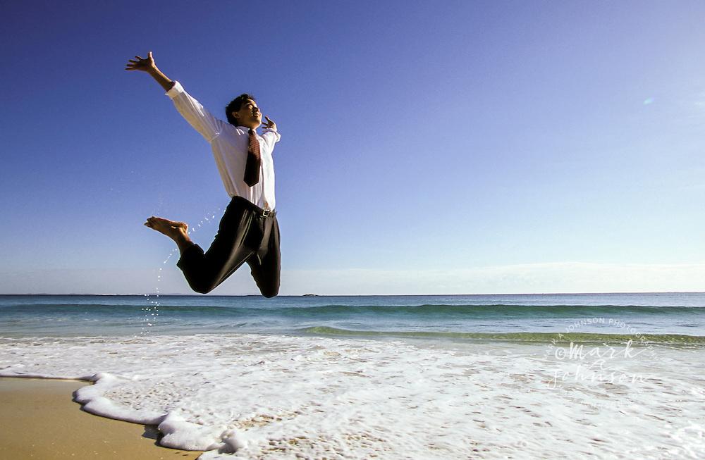 Australia, Queensland, businessman jumping in air on beach.