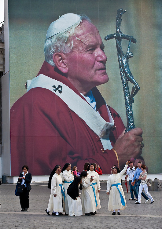 Religious sisters pose for photos at St. Peter's Square near a giant portrait of Pope John Paul II. (Sam Lucero photo)