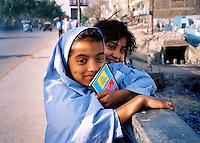 Pakistan, Karachi, 2004. Two young students take a break after school along one of Karachi's many bridges.