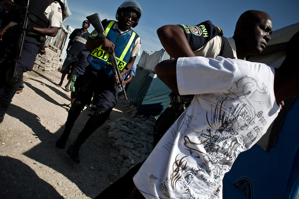 The presidential election in Haiti takes a bad way with fraud suspicions and troubles from some supporters in polling stations./// Policemen arrest man who threw stones against them, 28 november 2010 in a refugee camp of Port-au-Prince, during the vote for presidential election.