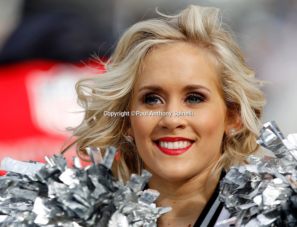 An Oakland Raiders cheerleader smiles as she does a dance routine during the NFL week 16 football game against the Indianapolis Colts on Sunday, December 26, 2010 in Oakland, California. The Colts won the game 31-26. (©Paul Anthony Spinelli)