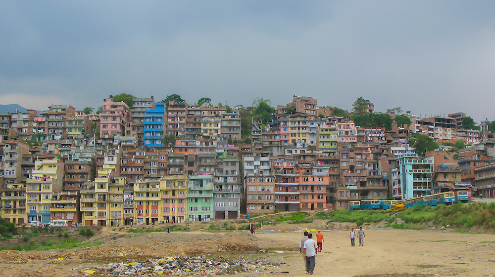 Men walking in front of some garbage a hill full with colorful houses, Nepal.