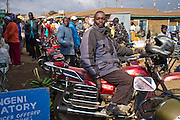 Pius Nyaga sits on his motorbike outside of Makongeni market, Thika, Kenya.  Pius helps Action for children in conflict, Afcic, out with transport. The market work closely with Afcic and are trying to encourage the kids to go to school. The manager has banned children from working in the market during school hours.
