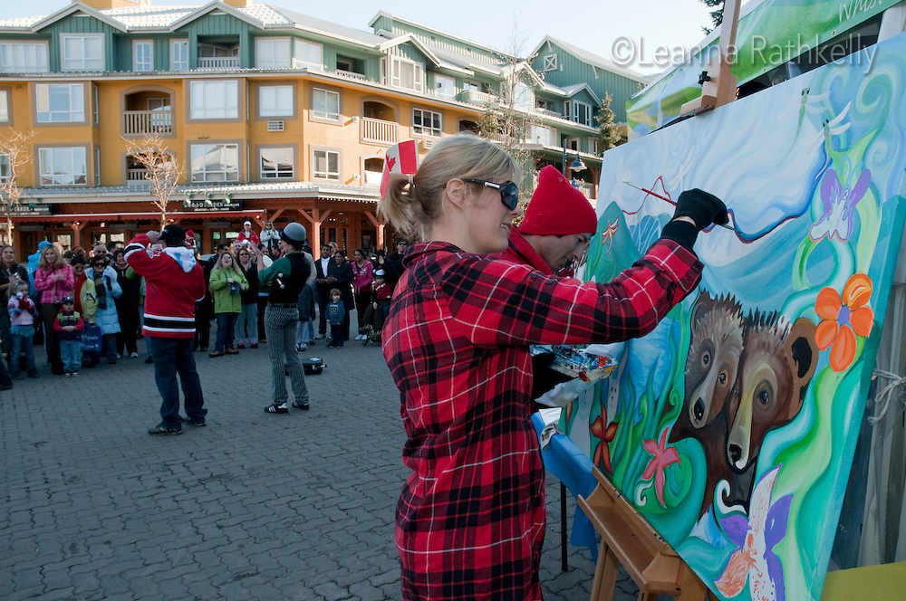 Artists Vanessa Stark and Oliver Roy paint in the Town Plaza while jugglers from Wonderbolt perform as part of Whistler Live during the 2010 Olympic Winter Games in Whistler, BC Canada.