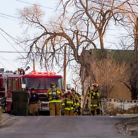 Gallup firefighters roll up a hose after extinguishing a brush fire on Victoria Avenue in Gallup early Tuesday.