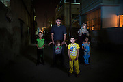 Ammar Mohammed Alajrab, 30, from the Bab Amur suburb of Homs, Syria, pictured with his family outside the building in which they rent a basement apartment, in Al Mafraq, Jordan, which they moved into after fleeing from Syria.<br /> <br /> The governor of Homs would collect money for the regime, they limit everything the people need, there are no generators, no water tanks, there is no electricity, but the Alawite community has everything. We were oppressed, we couldn't even mention then name of Bashar [Assad], then we saw the revolution in Tunis and Egypt and we were inspired by them.  Everyday we used to protest against the regime and the corruption, 300 people or more! When the regime saw this they sent soldiers and tanks to stop the gathering of people. They started to break into houses and interrogate the people and look for weapons. We were protesting in Homs at the same time as those in Deraa. <br /> <br /> People used to protest around the main clock in the center of Homs, then one night, at 1:30am, the army fired on the crowd, to this day no-one knows how many were killed. They [Syrian Army] entered my house one night at 4am, they broke the door down and ordered us to stand and face the wall. They had a list and they compared all the names with ours, they asked us, &quot;who are the protestors?&quot; They said I must co-operate and then hit me with a gun, they told us to get out of our own home. They stole from the abandoned houses: TVs, washing machines, food, money, jewellery. In the morning we found that everyone on the list had been taken away. <br /> <br /> After this we didn't feel secure. We didn't leave the house for twenty days, we were scared because there were checkpoints everywhere. My brother was detained and there was no sign of him for fifteen days, then we found him wandering. He had been tortured, for 1 month he didn't speak, he is here with me now but he has a disorder and cannot speak properly. After twenty days we left Homs because it was becoming like a ghost city. There was arbitra