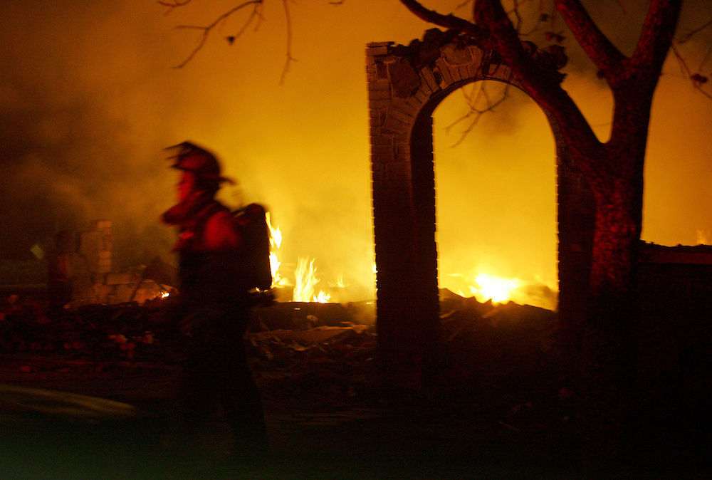 Photo © 2005 Alex Jones..A firefighter passes in front of the burning remains of a structure on Tuesday night, December 27, 2005, on Main street in Cross Plains, Texas after a massive fire swept through the town.