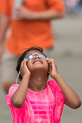 August 21, 2017 - Isle Of Palms, SC, United States of America - A young girl looks through special glasses as the total solar eclipse begins over the beach outside Charleston August 21, 2017 in Isle of Palms, South Carolina. The solar eclipse after sweeping across the nation crosses the Charleston area before heading over the Atlantic Ocean. (Credit Image: © Richard Ellis via ZUMA Wire)