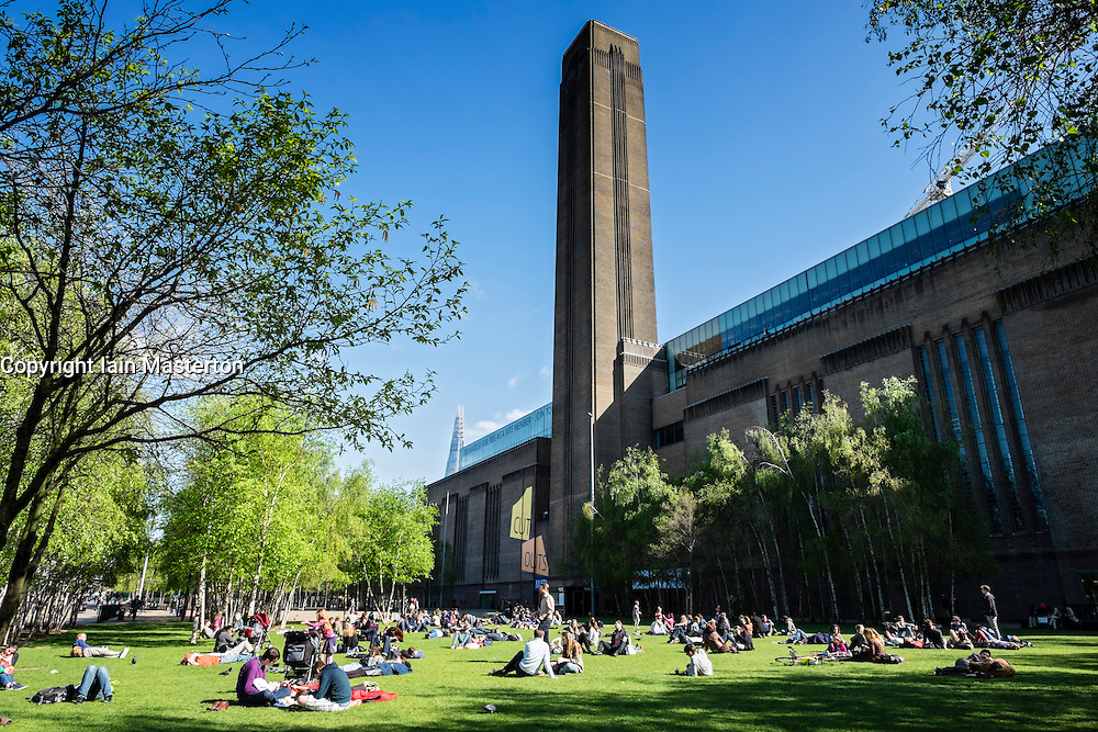 People relaxing on lawn outside Tate Modern art gallery in London United Kingdom