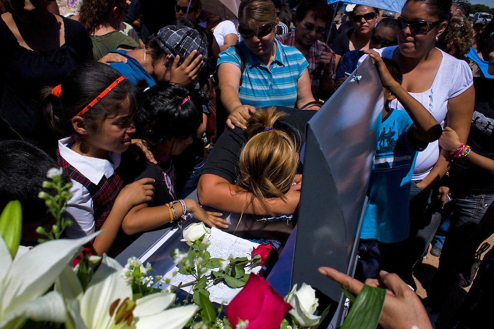 The wife of a Municipal Police officer throws herself on the casket  at his funeral in Ciudad Juarez, Chihuahua on May 21, 2010. The victim was 41-year-old municipal police officer, he was shot outside his home.