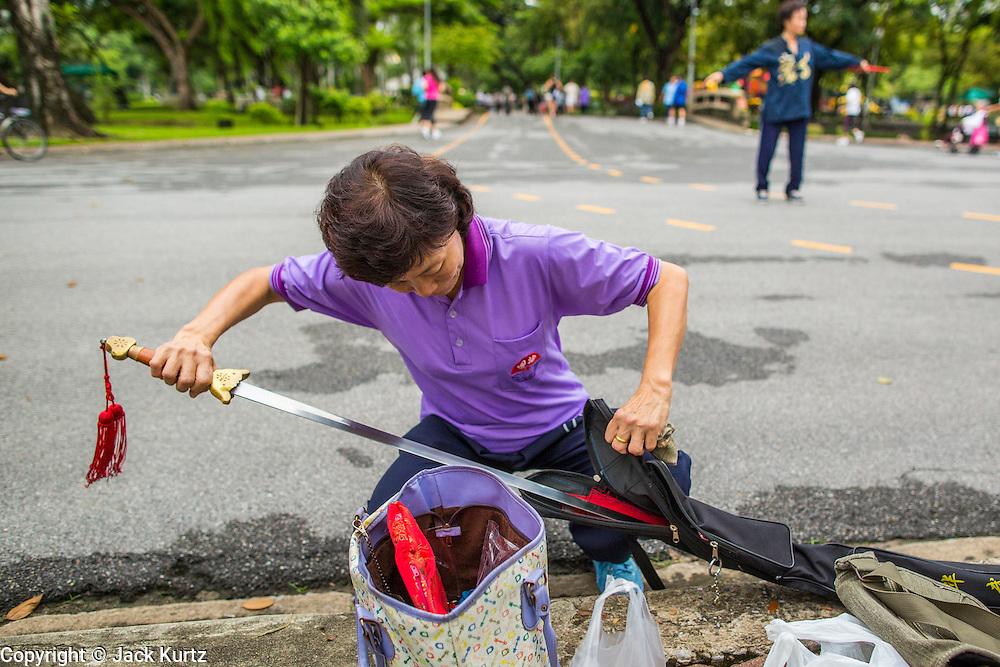 06 OCTOBER 2012 - BANGKOK, THAILAND:  A woman puts away her sword after doing Tai Chi exercises with it in Lumphini Park in Bangkok. The Thai government promotes exercise classes as a way staying healthy. Lumphini Park is 142 acre (57.6-hectare) park in Bangkok, Thailand. This park offers rare open public space, trees and playgrounds in the congested Thai capital. It contains an artificial lake where visitors can rent boats. Exercise classes and exercise clubs meet in the park for early morning workouts and paths around the park totalling approximately 1.55 miles (2.5 km) in length are a popular area for joggers. Cycling is only permitted during the day between the times of 5am to 3pm. Smoking is banned throughout smoking ban the park. The park was created in the 1920's and named after Lumbini, the birthplace of the Buddha in Nepal.   PHOTO BY JACK KURTZ