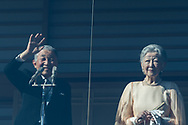 Japan's Emperor Akihito (L), flanked by Empress Michiko, is seen through a Japanese national flag as he waves to well-wishers who gathered at the Imperial Palace to mark his 84th birthday in Tokyo, Japan, December 23, 2017. 23/12/2017-Tokyo, JAPAN