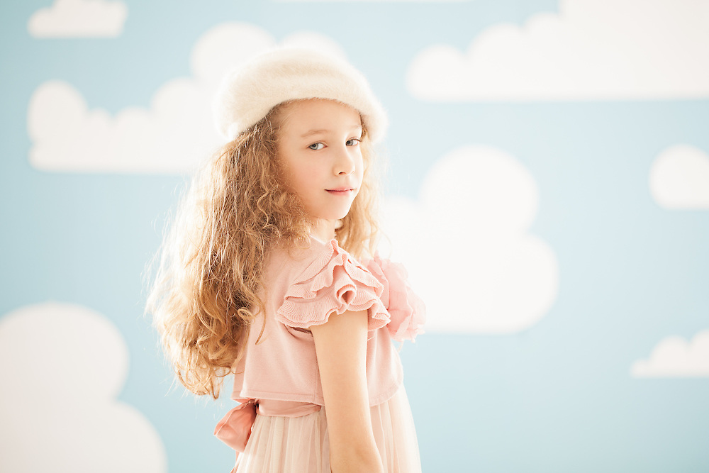 Cute girl posing in front of a blue background covered in clouds.