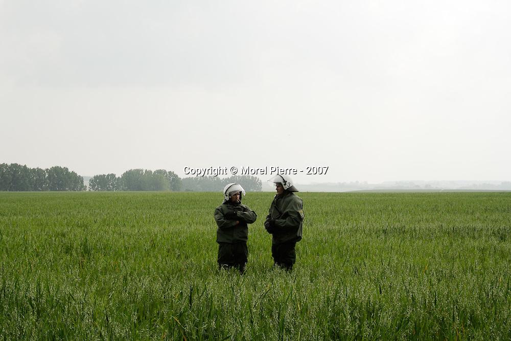 6 Juin - Porte Est de la zone rouge : Des policiers allemands attendent dans un champ près des manifestants.