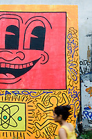 "2 August, 2008. New York, NY. A woman passes by the Keith Haring mural tagged by Angel Ortiz (with the nickname ""LA2"") and Clayton Patterson on July 22nd 2008. Angel Ortiz, 41, is a graffiti artist who collaborated with Keith Haring in the 80's. Mr Ortiz tagged his nickname ""LA2"", which refers to ""Little Angel"", on the Keith Haring mural that was reproduced on May 4th 2008, after the original 1982 graffiti was painted over. Angel Ortiz asked Clayton Patterson, an artist and gallerist, to help him tag the wall with his own artwork. Mr. Ortiz has accused the Haring Foundation of denying him credit on many of the jointly produced works.  The two artists met in 1980, when Angel Ortiz was 13 years old. Subsequently, Ortiz and Haring collaborated for several years and had joint shows. <br />  ©2008 Gianni Cipriano for The New York Times<br /> cell. +1 646 465 2168 (USA)<br /> cell. +1 328 567 7923 (Italy)<br /> gianni@giannicipriano.com<br /> www.giannicipriano.com"