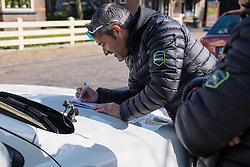 Manel Lacambra checks out the competition on the start list - Drentse 8, a 140km road race starting and finishing in Dwingeloo, on March 13, 2016 in Drenthe, Netherlands.