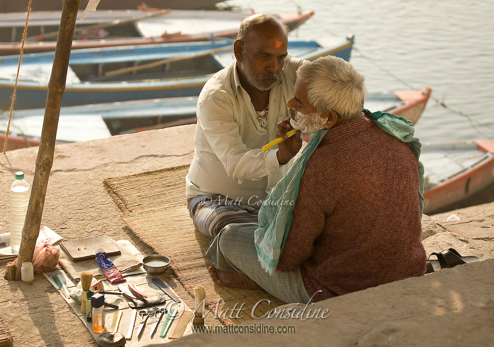 Barber shaving beard of old man on the ghats of River Ganges in Varanasi.<br /> (Photo by Matt Considine - Images of Asia Collection)
