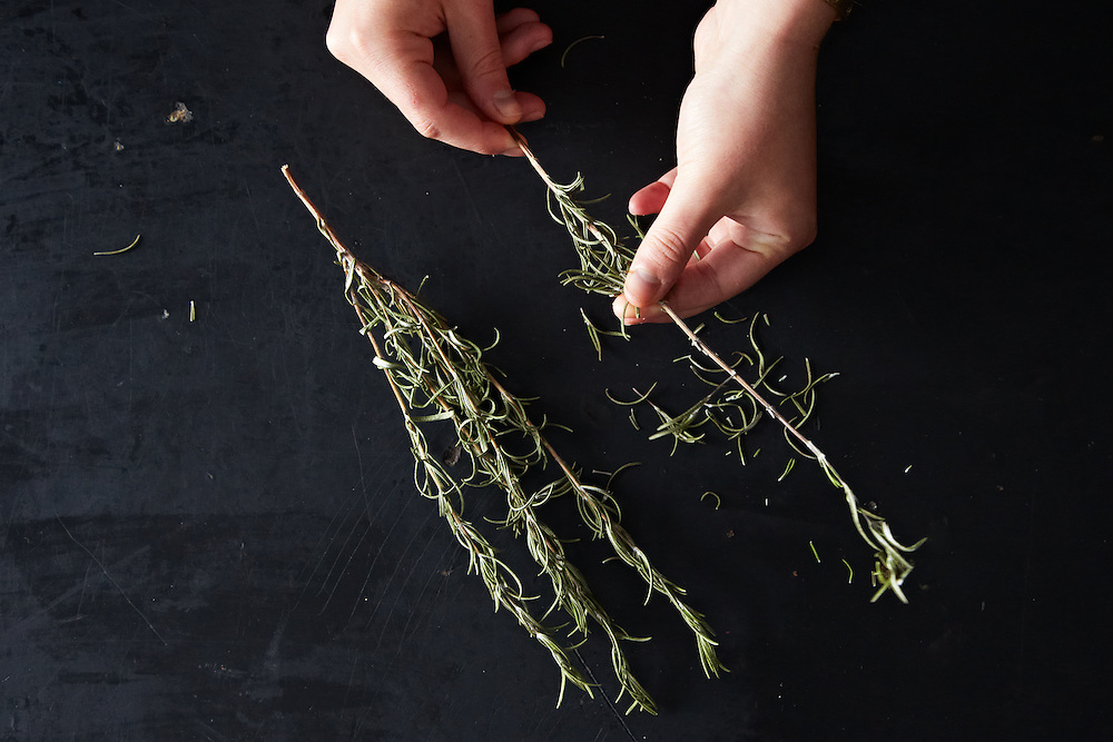 Hands removing dried rosemary from stems.