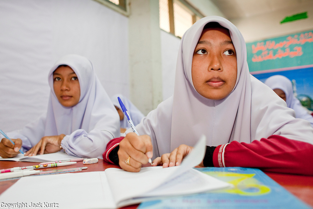 "Sept. 29, 2009 -- SAI BURI, THAILAND: Girls in a math class at the Darunsat Wittya Islamic School in Sai Buri, Thailand. The school is the largest Muslim high school in Pattani province. Although it is a private school, the Thai government pays students' tuition to attend the school. The curriculum combines Thai official curriculum with Islamic curriculum. Many of the students go on to college level education in Egypt and Saudi Arabia. The Thai government views Islamic high schools with suspicion, fearing they radicalize students. Thailand's three southern most provinces; Yala, Pattani and Narathiwat are often called ""restive"" and a decades long Muslim insurgency has gained traction recently. Nearly 4,000 people have been killed since 2004. The three southern provinces are under emergency control and there are more than 60,000 Thai military, police and paramilitary militia forces trying to keep the peace battling insurgents who favor car bombs and assassination.   Photo by Jack Kurtz / ZUMA Press"