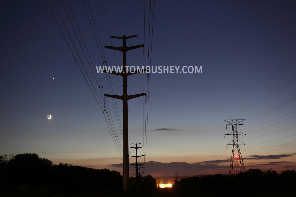 Middletown, New York - A crescent moon, at left, and Venus, above the moon, shine behind power lines on the evening of June 14, 2010. The two bright stars at the center, on either side of the tower, are Pollux and Castor of the constellation Gemini.