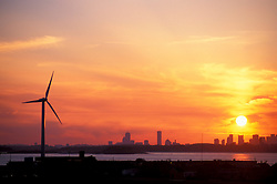 Wind Turbine in Hull, Massachusetts.  The Boston skyline is in the distance. Sunset.