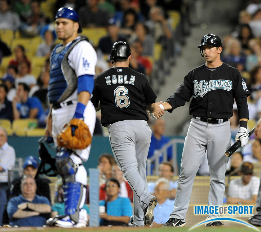 Jul 12, 2008; Los Angeles, CA, USA; Florida Marlins second baseman Dan Uggla (6), center, is greeted by John Baker (53), right, after scoring on a sacrifice fly in the 10th inning by Cory Ross (not pictured) as Los Angeles Dodgers catcher Russell Martin (55), left, watches at Dodger Stadium.