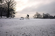 © Licensed to London News Pictures. 03/02/2015. Richmond, UK. A man rides a bike through a snow covered meadow.  People in snow in Richmond Park, South West London today 3rd February 2015. Snow fell across the London area overnight . Photo credit : Stephen Simpson/LNP