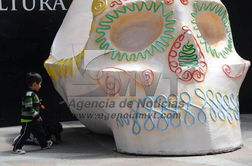 Toluca, México.- Como parte de los inicio de las festividades de día de Muertos, niños juegan y se toman la foto del recuerdo junto a una calavera gigante dentro en el ágora de la plaza González Arratia. Agencia MVT / Arturo Hernández.