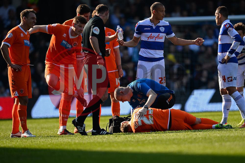 Blackpool's midfielder James Caton gets treatment for an injury - Photo mandatory by-line: Mitchell Gunn/JMP - Tel: Mobile: 07966 386802 29/03/2014 - SPORT - FOOTBALL - Loftus Road - London - Queens Park Rangers v Blackpool - Championship