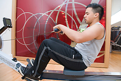 Young man using a rowing machine at gym,