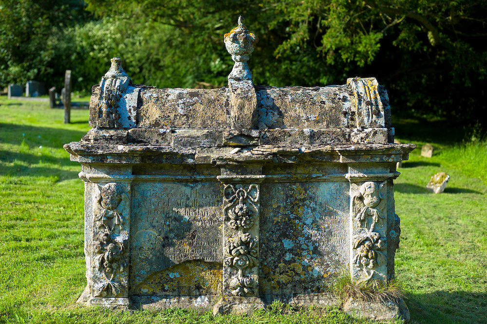 Ancient tomb with lichens in graveyard burial ground at St Nicholas Church in Asthall in The Cotswolds, Oxfordshire, UK