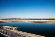 """A water reservoir at La Dehesa solar power plant. La Dehesa, 50 MW parabolic through solar thermal power plant with molten salts storage. Completed in February 2011, it is located in La Garovilla (Badajoz), Spain, and it is owned by Renovables SAMCA. With an annual production of 160 million kwh, La Dehesa will be able to cover the electricity needs of more than 45,000 homes, preventing the emission of 160,000 tons of carbon. The 220 h plant has 225,792 mirrors arranged in rows and 672 solar collectors wich occupy a total length of 100km."""",""""- solar field formed by the fluid and the fluid circulation system."""