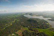 Aerial view over tank, forest and paddy lands and hills.