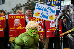 "© Licensed to London News Pictures. 17/09/2019. London, UK. A protester wearing a ""Hulk"" face mask demonstrate outside UK Supreme Court in London as the court begins a three day appeal hearing in the multiple legal challenges against the Prime Minister Boris Johnson's decision to prorogue Parliament ahead of a Queen's speech on 14 October. Eleven instead of the usual nine Supreme Court justices will hear the politically charged claim that Boris Johnson acted unlawfully in advising the Queen to suspend parliament for five weeks in order to stifle debate over the Brexit crisis. It is the first time the Supreme Court has been summoned for an emergency hearing outside legal term time. Lady Hale, the first female president of the court who retires next January, will preside. Photo credit: Dinendra Haria/LNP"