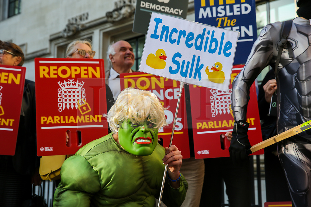 """© Licensed to London News Pictures. 17/09/2019. London, UK. A protester wearing a """"Hulk"""" face mask demonstrate outside UK Supreme Court in London as the court begins a three day appeal hearing in the multiple legal challenges against the Prime Minister Boris Johnson's decision to prorogue Parliament ahead of a Queen's speech on 14 October. Eleven instead of the usual nine Supreme Court justices will hear the politically charged claim that Boris Johnson acted unlawfully in advising the Queen to suspend parliament for five weeks in order to stifle debate over the Brexit crisis.It is the first time the Supreme Court has been summoned for an emergency hearing outside legal term time.Lady Hale, the first female president of the court who retires next January, will preside. Photo credit: Dinendra Haria/LNP"""