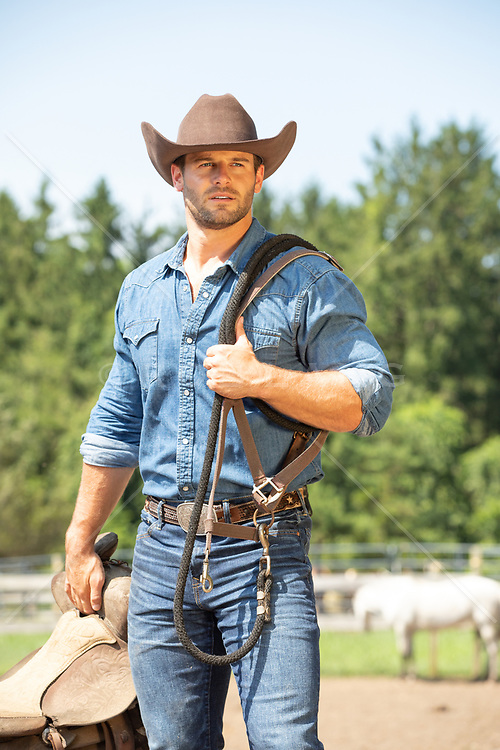 rugged cowboy with a saddle and reins on a ranch