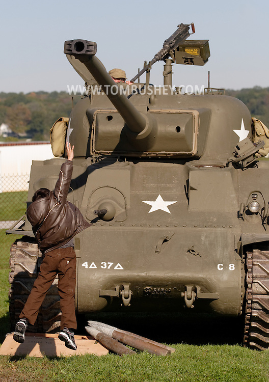 Montgomery, N.Y. - A boy jumps in an attempt to  touch part of a Sherman tank on display at Orange County Airport on Sept. 29,  2006.