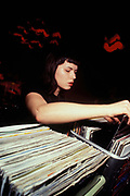 Female DJ selecting vinyl, Prague, Czech Republic, 1998.