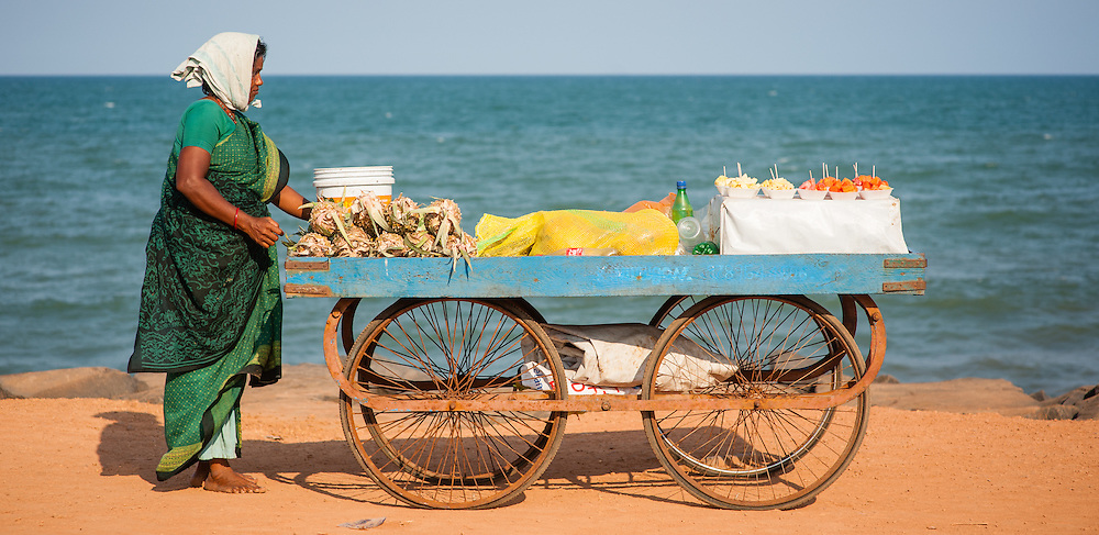 Woman pushing snack stall by the sea at Puducherry (India)