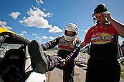 Crew member Kahlen Koch of Post Falls, right, gives Charlie Imus, left, a hand into the number twenty race car on Sunday afternoon at Stateline Stadium and Speedway.