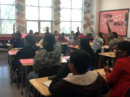Lora B. Peck students eagerly answer a teacher's question in class.