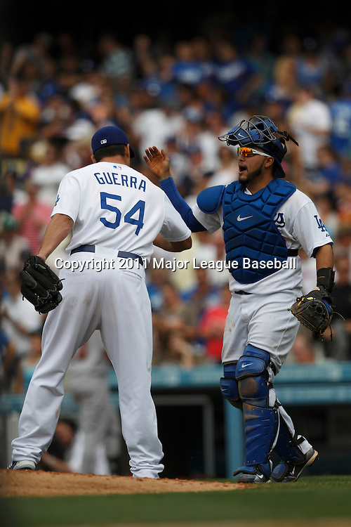 LOS ANGELES - JUNE 19:  Catcher Dioner Navarro #30 of the Los Angeles Dodgers gives closing pitcher Javy Guerra #54 a high five after the closer wins the game against the Houston Astros at Dodger Stadium on Sunday, June 19, 2011 in Los Angeles, California.  The Dodgers defeated the Astros 1-0.  (Photo by Paul Spinelli/MLB Photos via Getty Images) *** Local Caption *** Dioner Navarro;Javy Guerra