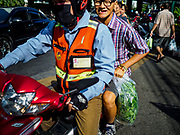 20 JUNE 2018 - BANGKOK, THAILAND:  A passenger on a motorcycle taxi with a plastic bag of basil at Makkasan Market, a small local market in central Bangkok. Officials in Thailand are wrestling with Thais use of plastic bags. The issue became a very public one in early June when a whale in Thai waters died after ingesting 18 pounds of plastic. In a recent report, Ocean Conservancy claimed that Thailand, China, Indonesia, the Philippines, and Vietnam were responsible for as much as 60 percent of the plastic waste in the world's oceans.     PHOTO BY JACK KURTZ