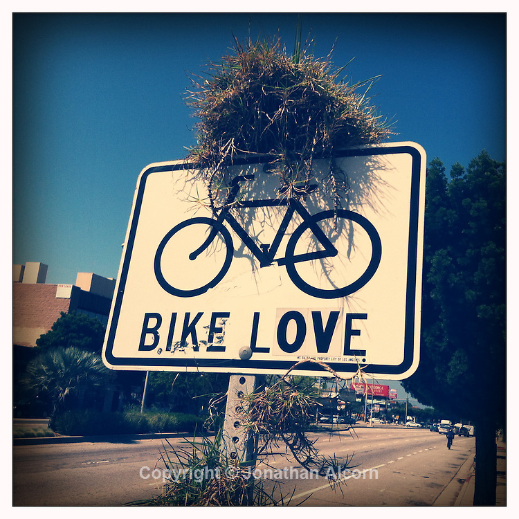 "Grass grows on a Bike Lane sign modified to read ""Bike Love"" on Venice Blvd in Los Angeles, California on May 14, 2012."