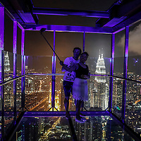 A couple take a selfie inside a skybox (300m above sea level) over a Kuala Lumpur night scene during the supermoon night at Kuala Lumpur Tower, Kuala Lumpur, Malaysia, 14 November 2016.